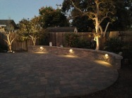 Backyard hardscape with landscape lighting under the sitting wall and in the planter (Camarillo)